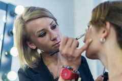 Make-up artist doing smoky eyes makeup to beautiful young girl Royalty Free Stock Photography