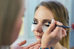 Make-up artist doing smoky eyes makeup to beautiful young girl Stock Image
