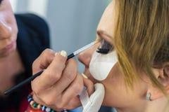 Make-up artist doing smoky eyes makeup to beautiful young girl Stock Photos