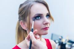 Make-up artist doing smoky eyes makeup to beautiful young girl Stock Photo
