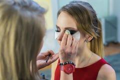 Make-up artist doing smoky eyes makeup to beautiful young girl Stock Photography