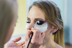 Make-up artist doing smoky eyes makeup to beautiful young girl Royalty Free Stock Images