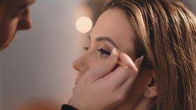 The make-up artist gently applies a black matte eyeliner to the eyelids, a professional brush on the face of a Caucasian. Blonde model. Profile view. Close-up stock footage