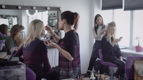 Make-up artist and hairdresser of famous beauty shop are working in tandem with two models preparing for future shooting stock video