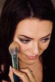 Make-up artist hand applying bright base color on model`s face and holding a brush , close . Royalty Free Stock Photo