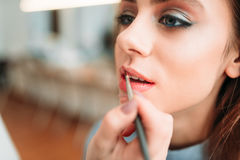 Make up artist hand applying gloss on woman lips. Make up artist hand with brush applying gloss on woman lips. Professional female beautician work with glamour Stock Photo