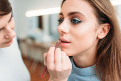 Make up artist hand applying gloss on woman lips. Make up artist hand with brush applying gloss on women lips. Professional female beautician work with glamour Royalty Free Stock Images