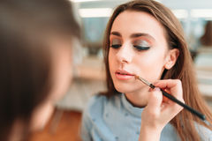 Make up artist hand applying gloss on woman lips. Make up artist hand with brush applying gloss on women lips. Professional female beautician work with glamour Royalty Free Stock Image