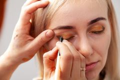 The make-up artist with the help of a pencil in one hand draws an arrow on the eyes of the model, with the other hand pulls back stock photography