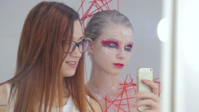 Make up artist and her client with creative unusual make-up taking selfie. White makeup room. Beauty, fashion and technology concept stock footage