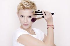 Make-up artist holding brushes royalty free stock photo