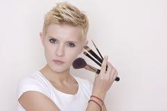 Make-up artist holding brushes stock photo