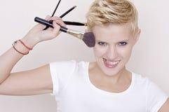 Make-up artist holding brushes royalty free stock images