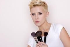 Make-up artist holding brushes stock photos