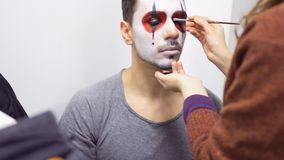 Make-up artist makes greasepaint on man`s face before his performance on scene. Professional worker draws man`s face with paint and brush. Prores codec stock footage