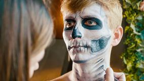 Make-up artist makes the guy halloween make up. Halloween male face art. stock photos