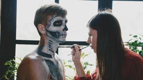 Make-up artist makes the guy halloween make up. Halloween male face art. stock photo