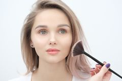 Make-up artist makes makeup beautiful blonde girl on a white background. Close-up hands with brush and face. stock image
