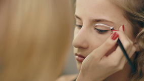 Make-up artist makes young actress girl beautiful makeup for eyes before dancing perfomance indoors stock footage