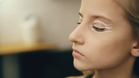 Make-up artist makes young actress girl beautiful makeup for face before dancing perfomance indoors stock video