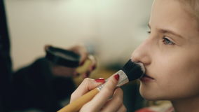 Make-up artist makes young actress girl beautiful makeup for face before dancing perfomance indoors stock footage