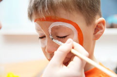 Make up artist making tiger mask for child.Children face painting. Boy  painted as tiger or ferocious lion. Preparing for theatre Royalty Free Stock Photography