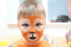 Make up artist making tiger mask for child.Children face painting. Boy  painted as tiger or ferocious lion Royalty Free Stock Photography