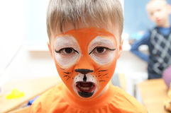 Make up artist making tiger mask for child.Children face painting. Boy  painted as tiger or ferocious lion. Preparing for theatrical performance. Boy actor Royalty Free Stock Images