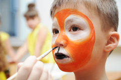 Make up artist making tiger mask for child.Children face painting. Boy  painted as tiger or ferocious lion. Preparing Royalty Free Stock Image