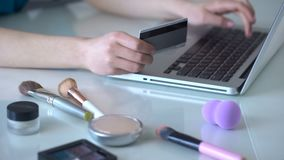 Make-up artist ordering new cosmetics online, typing data of her credit card