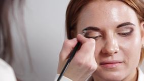 Make-up artist is painting over a brows of girl by brush and shadows stock video footage