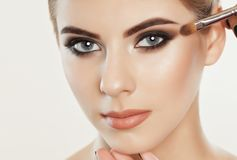The make-up artist paints eyebrows and eyes to a beautiful girl royalty free stock photography