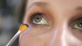 The make-up artist paints eyelashes of the lower eyelid with a professional tassel. Girl model with blue eyeliner on the stock video