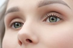 Make-up artist paints a girl with black mascara eyelashes closeup. stock image