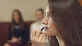 Make-up artist paints the lips to a young girl. stock video footage