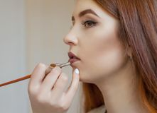 The make-up artist paints the lips of a young girl with lipstick in a beauty salon. Professional skin care stock image