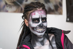 Make-up artist paints the skull on the girl`s face Stock Photography
