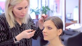 Make-up artist put make-up to model using mascara stock footage