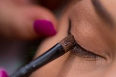 Make-up artist puts eye liner on woman`s eye in the salon stock photos