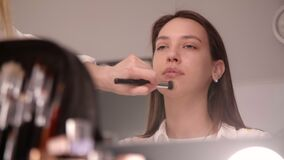 Make-up artist puts on a foundation on a model's face
