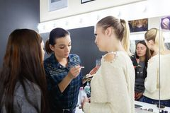 Make-up artist puts on make-up on girl model face Stock Photography
