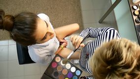 The make-up artist puts on the make-up on the client. Shooting from the top view. stock video footage