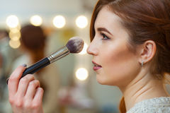 Make-up artist puts powder on the face of a beautiful, red-haired girl in the beauty salon. Professional cosmetics, make-up and skin care stock photo
