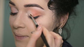 Make-up artist putting on makeup on model`s eyes. stock video footage