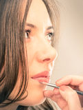 Make-up artist refining lips of a beautiful young Model Stock Image