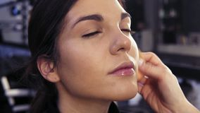 Make up artist`s hand applying foundation on previously prepared face of an attractive brunette girl in a beauty salon stock video