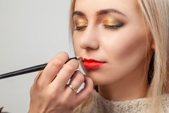 The make-up artist in the studio imposes a luxurious oriental make-up to a young girl blonde, in whose hand she brushes a lipstick royalty free stock images