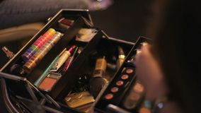 Make-up artist takes cosmetics from her suitcase. Professional cosmetics makeup artist in a suitcase. Multicolored stock footage