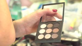 Make-up artist taking eye shadows from multicolor make-up eyeshadows palette in beauty salon. Closeup of colourful stock video footage