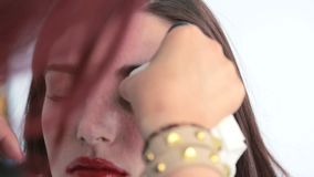 Make up artist taking off models eye makeup stock video